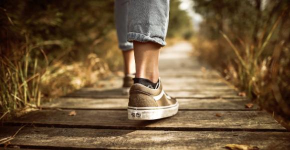 woman's shoes and lower legs walking on board walk.